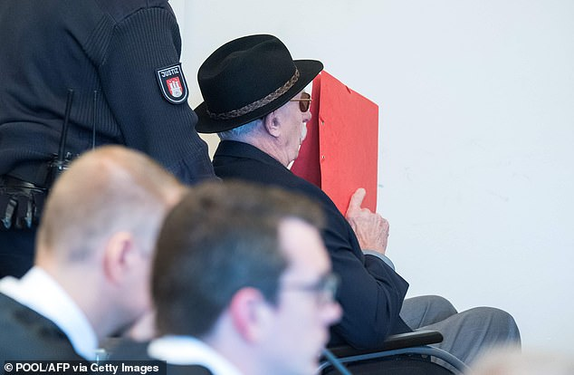 93-year-old former SS guard Bruno Dey covers his face in the courtroom during his trial in Hamburg.Dey stands accused of involvement in the murder of 5,230 people when he worked at the Stutthof concentration camp near what was then Danzig, now Gdansk in Poland