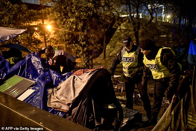 Migrants are evacuated by the police from a camp in northern Paris early on Thursday