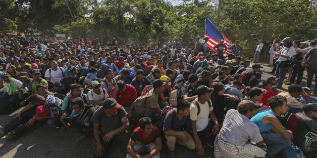 Migrants sit on the highway leading to Tapachula, Mexico on Thursday, where they are blocked by National Guardsmen. (AP Photo/Marco Ugarte)