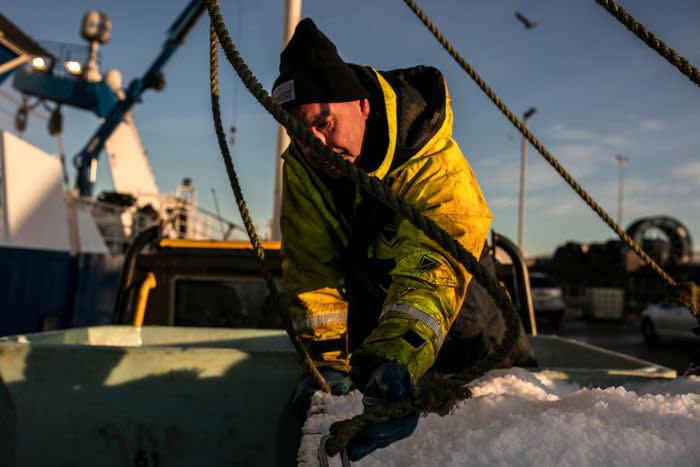 Crew members prepare their vessel to leave Peterhead harbour