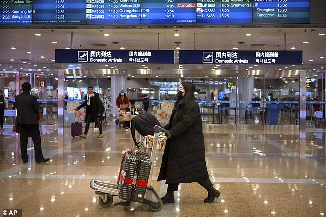 The CDC issues its highest travel warning on Thursday, urging Americans to 'avoid unessential travel' to Wuhan as the new coronavirus has left more than 600 sick and 18 dead. Pictured: Travelers in face masks walk past a display board showing a canceled flight from Wuhan at Beijing Capital International Airport on Thursday
