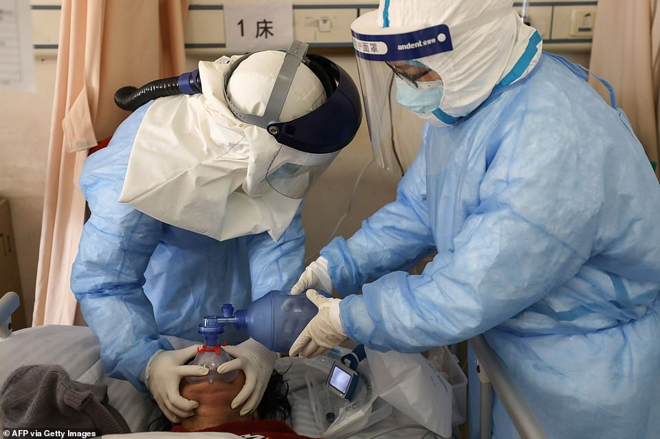 Medical staff members treating a patient infected by the COVID-19 coronavirus at the Wuhan Red Cross Hospital in Wuhan in China's central Hubei province