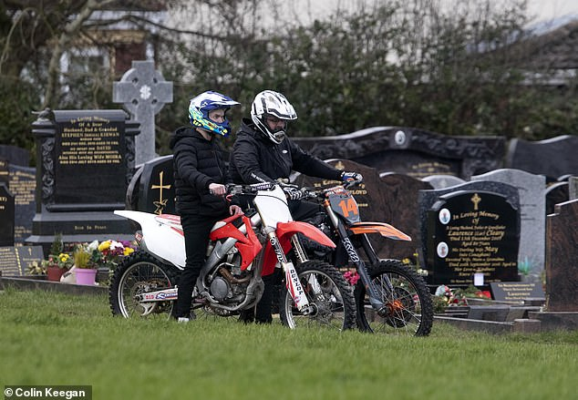 Mourners on motocross bikes ride through Calvary Cemetery at the funeral today where a priest condemned the killers' 'appalling wickedness and evil'