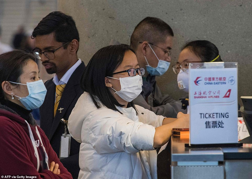 Another 34 people were stopped at preclearance locations at foreign airports where US officials screen travelers before letting them board flights to America. Pictured:Passengers wear masks as they wait for standby tickets on a China Eastern flight to Shanghai, at Los Angeles International Airport, California, on February 2