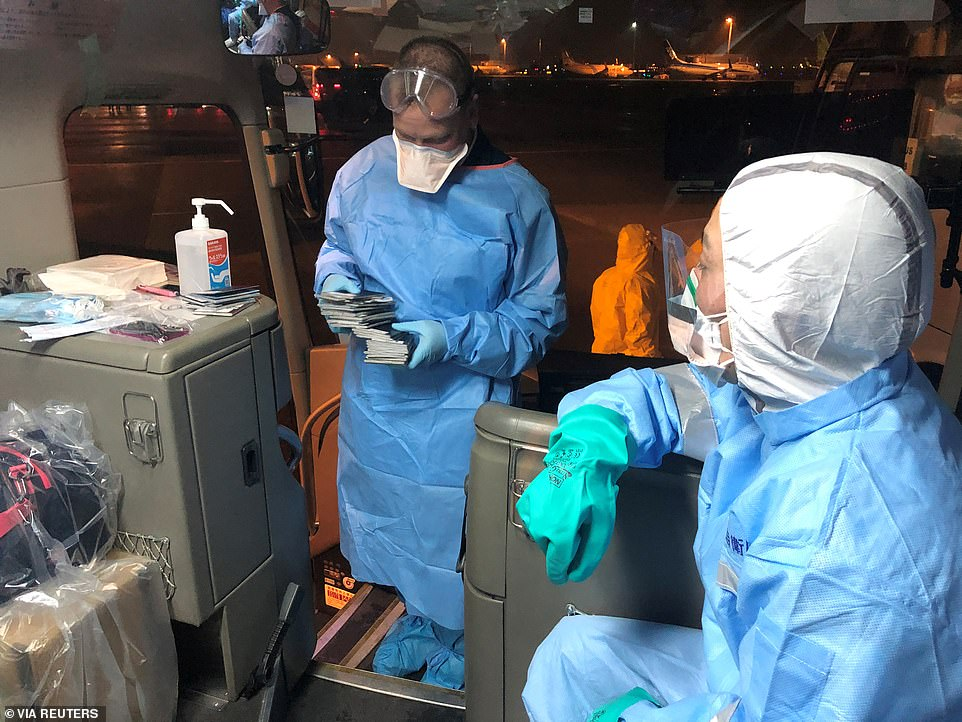 Health officials in protective suits are seen ferrying passengers to board the evacuation flights in Tokyo