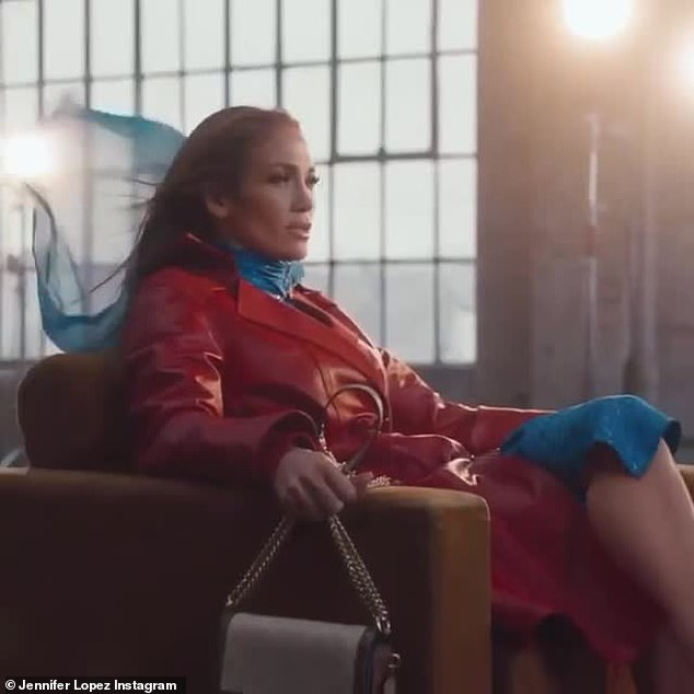 Coached out:In the clip Jennifer has on a red trench coat with a wide belt and buckle, front pockets as well as a blue shirt and scarf. She holds a Coach purse in brown