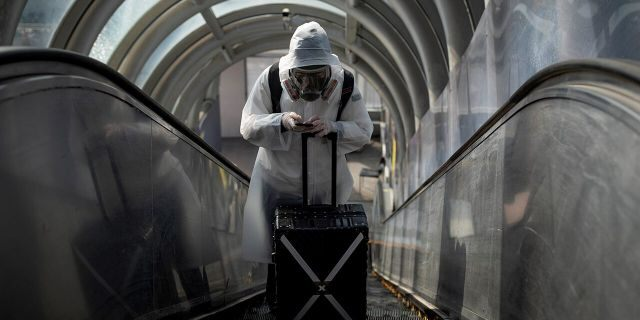 A traveler wearing protective clothing and a full-face mask goes up an escalator after leaving Beijing Railway Station as the country is hit by an outbreak of the novel coronavirus disease (COVID-19), China, March 20, 2020. REUTERS/Thomas Peter