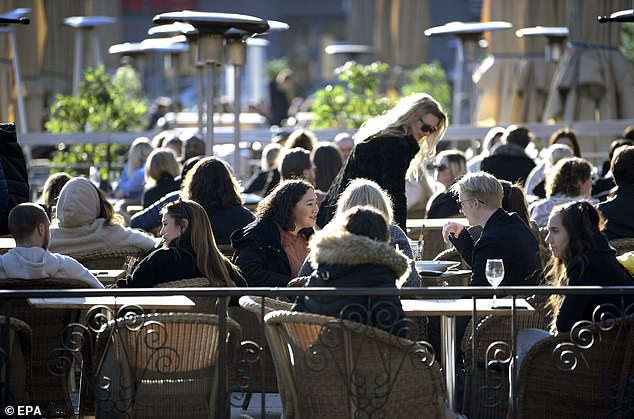 People sit in close proximity at an outdoor restaurant in central Stockholm last Thursday, well after most of Sweden's neighbours had imposed drastic lockdowns