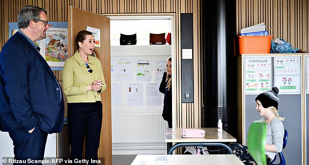 Danish Prime Minister Mette Frederiksen speaks with a pupil as she participates in the reopening of Lykkebo School in Valby in Copenhagen