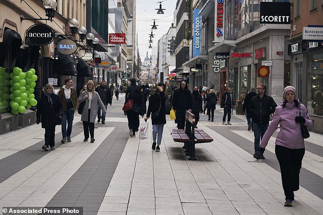 People walk along the main pedestrian shopping street in Stockholm last Wednesday, as the Swedish government takes a lighter touch than most of its counterparts