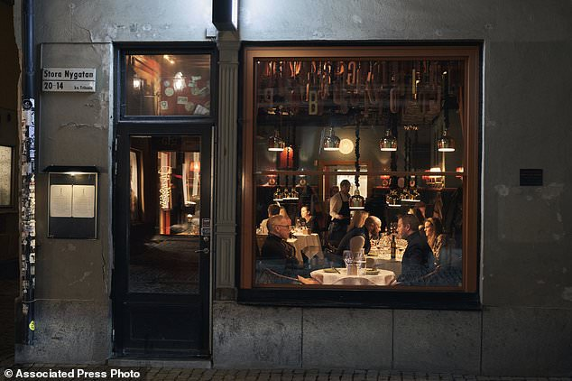 People sit in a restaurant in Stockholm last Wednesday, without the ban on public gatherings or enforced social distancing that is in place in many countries