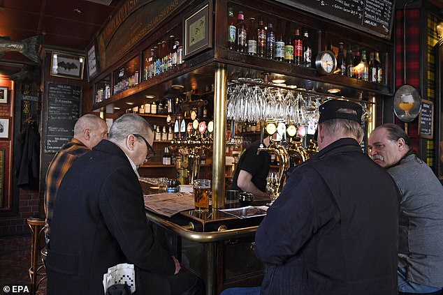 Patrons of the Half Way In pub in Stockholm gather for a drink on March 23, the day Boris Johnson announced severe restrictions in the UK