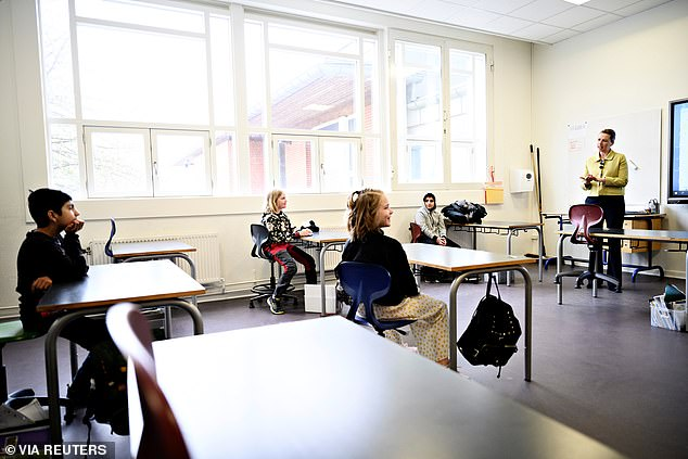 Danish Prime Minister Mette Frederiksen speaks with pupils as she attends the reopening of Lykkebo School in Valby. Special rules mean desks must be kept at least six feet apart