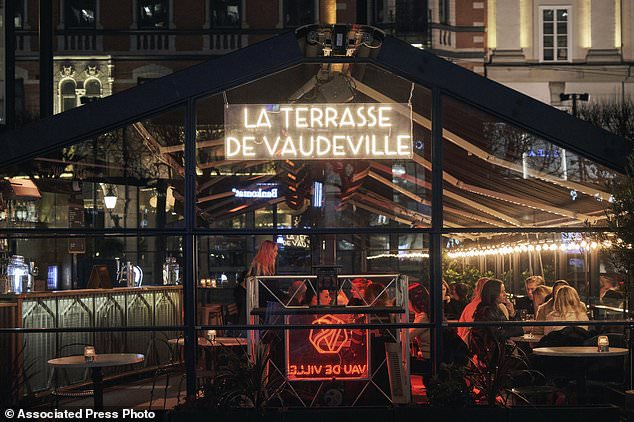 People sit in a bar in Stockholm last Wednesday, in a social gathering which has been banned in countries such as France and Italy for more than two weeks