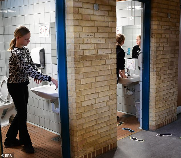 Pupils wash their hands during a break at Korshoej school in Randers, Denmark