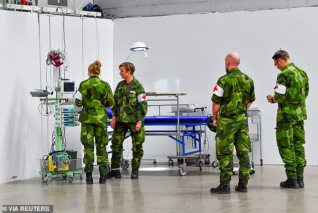 Members of Sweden's armed forces build a field hospital inside the Stockholmsmassan exhibition center in the capital which will provide intensive care space