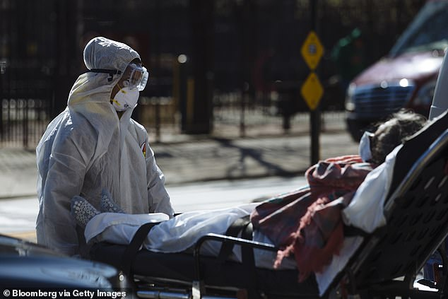 Poison control centers have seen an uptick in children accidentally ingesting hand sanitizers found in their homes. Pictured:A medical worker pushes a stretcher outside Elmhurst Hospital Center in Queens, New York, March 26