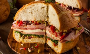 A muffuletta sandwich with meat, cheese and olives.