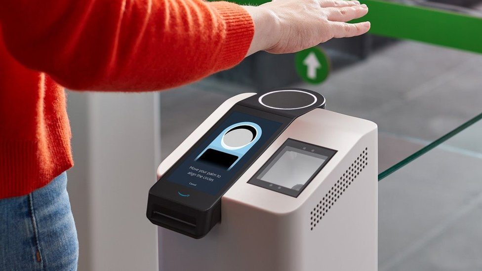 """A person's arm and torso in frame show them holding a hand over a scanning terminal which has a ring pointing upwards, and the instruction to """"move your palm to align the circles"""""""
