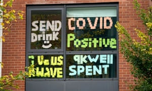 Signs made by students are displayed in a window of their locked down accommodation building  in Manchester, England