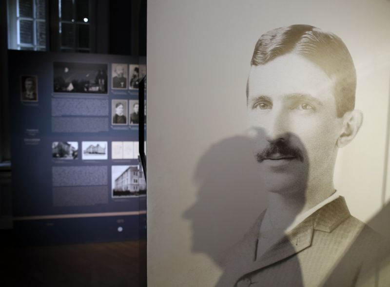 In this Thursday, March 7, 2019 file photo, a shadow of Milica Kesler, curator and archivist is cast onto a poster of Nikola Tesla at the Nikola Tesla museum in Belgrade, Serbia. (AP Photo/Darko Vojinovic)