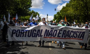 "André Ventura with banner reading ""Portugal is not racist"""