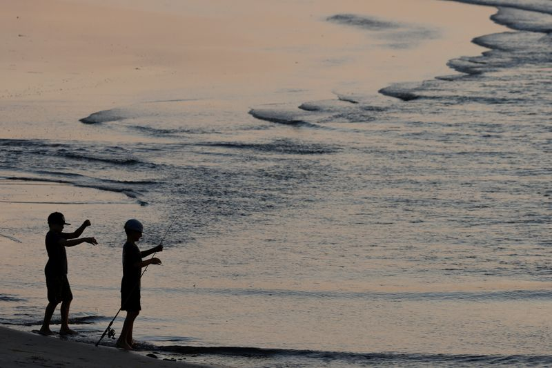 © Reuters. Two boys fish at Cardiff State Beach