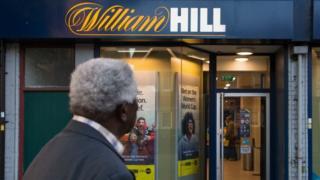 Man looking at William Hill shopfront