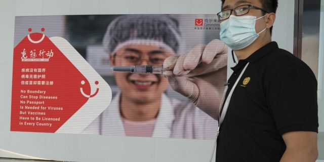 An employee of SinoVac stands near an advertisement for its SARS CoV-2 Vaccine for COVID-19 named CoronaVac at its factory in Beijing on Thursday, Sept. 24, 2020. SinoVac's CEO says they have injected 90 percent of its employees and family members, or about 3,000 people, and provided tens of thousands of rounds of CoronaVac to the municipal government of Beijing. It's a highly unusual move that raises ethical and safety questions, as companies and governments worldwide race to develop a vaccine that will stop the spread of the new coronavirus. (AP Photo/Ng Han Guan)