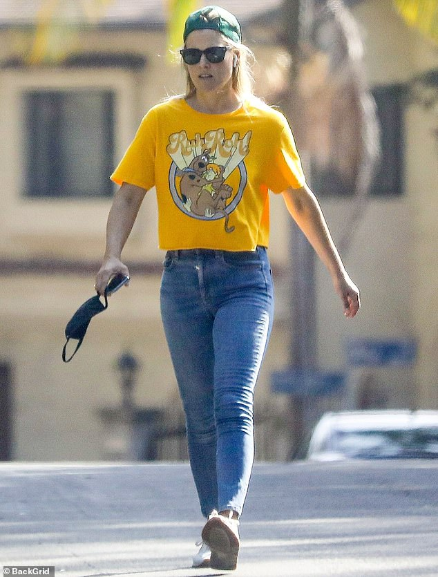 Staying safe: As she displayed her trim waist in a pair of light-wash jeans, the 44-year-old actress sported a radiant glow and clutched a CDC-recommended face mask in one hand