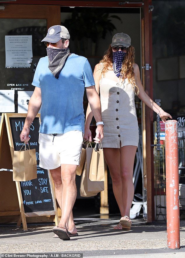 Goodies:The duo were first leaving a shop with bags in tow, with Jon wearing a blue shirt with shorts, adding a baseball cap, bandanna as a mask and flip flops