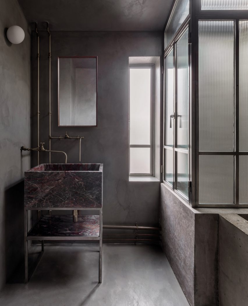 Concrete bathroom, stone sink and Crittal screen of bathroom in Untiled House extension by Szczepaniak Astridge in London