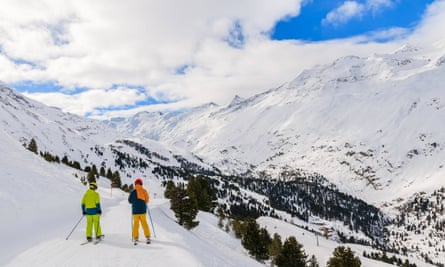 Two skiers on beautiful slope and mountain valley in winter season in Hochgurgl-Obergurgl ski area, Tirol, Austria