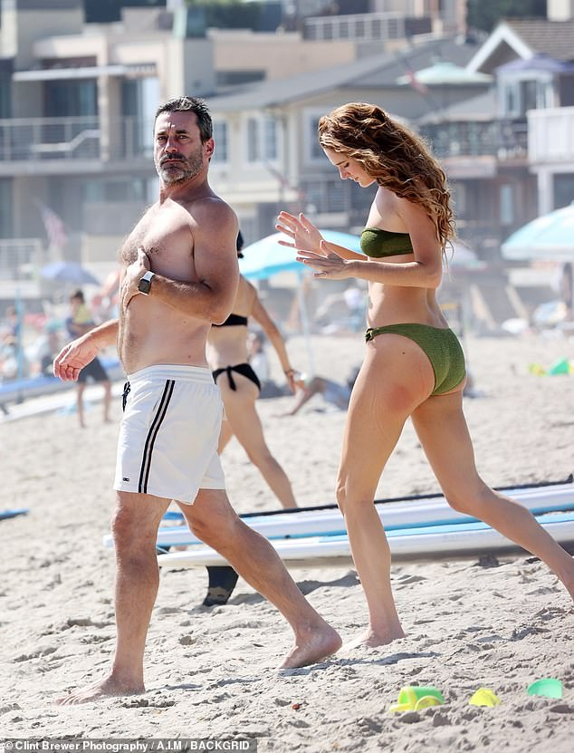 Going in the water:The TV star donned white swim trunks with black accents on it while flashing his sculpted form