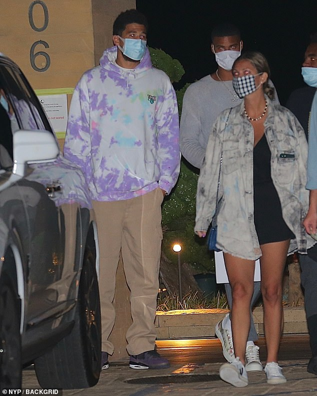 Casual look: Devin paired a tie-dye purple hoodie with beige trousers for the outing