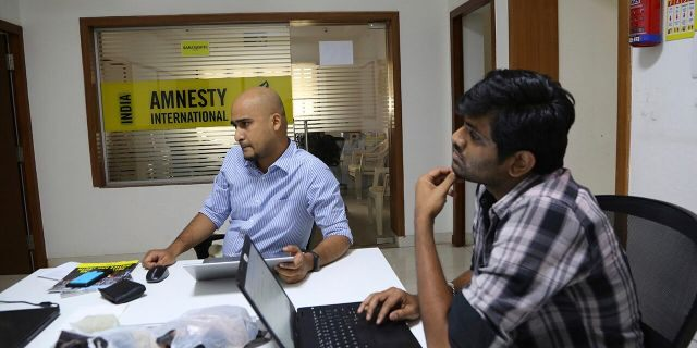 FILE - In this Tuesday, Feb. 5, 2019, file photo, Amnesty International India employees work at their headquarters in Bangalore, India. (AP Photo/Aijaz Rahi, File)