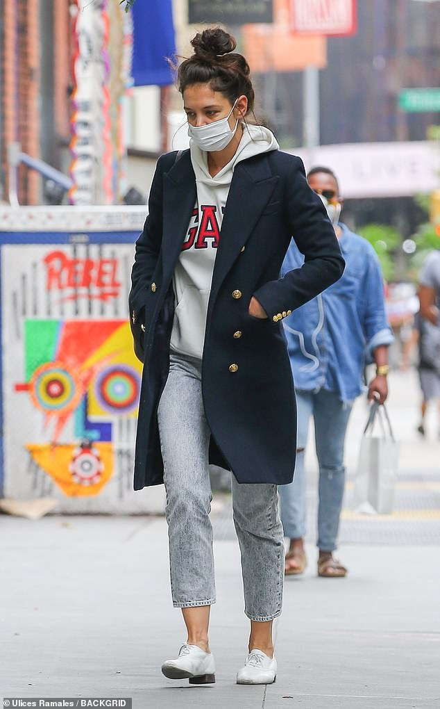 Keeping it casual: Despite sporting a messy top knot, the street style icon dressed up her laid-back look with a chic structured navy jacket with gold buttons