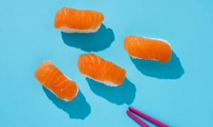 high-angle shot of some nigiri sushi and a pair of chopsticks on a blue table