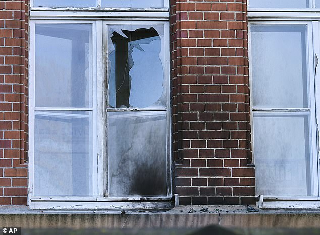 A broken window and blackened facade at the Robert Koch Institute's offices in Berlin on Sunday after a mysterious arson attack