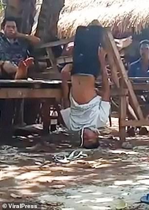 Mario Natriti, 23, is pictured hanging upside-down inEast Nusa Tenggara, Indonesia