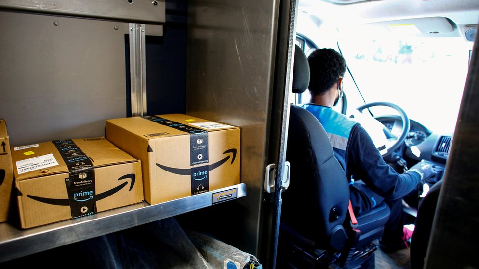 driver in mask with Amazon boxes