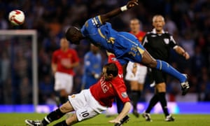 Sol Campbell and Wayne Rooney battle for possession during Manchester United's 1-0 victory over Portsmouth at Fratton Park in August 2008