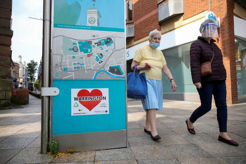 © Reuters. Women wearing a protective mask and a face shield walk past a city map, in Warrington