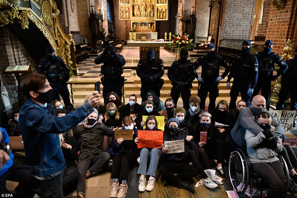 Protesters targeted Catholic churches across Poland on Sunday in the fourth straight day of upheaval against a near-total ban on abortion in the Catholic EU country. Pictured:People take part in a protest at the Archcathedral Basilica of St. Peter and St. Paul in Poznan