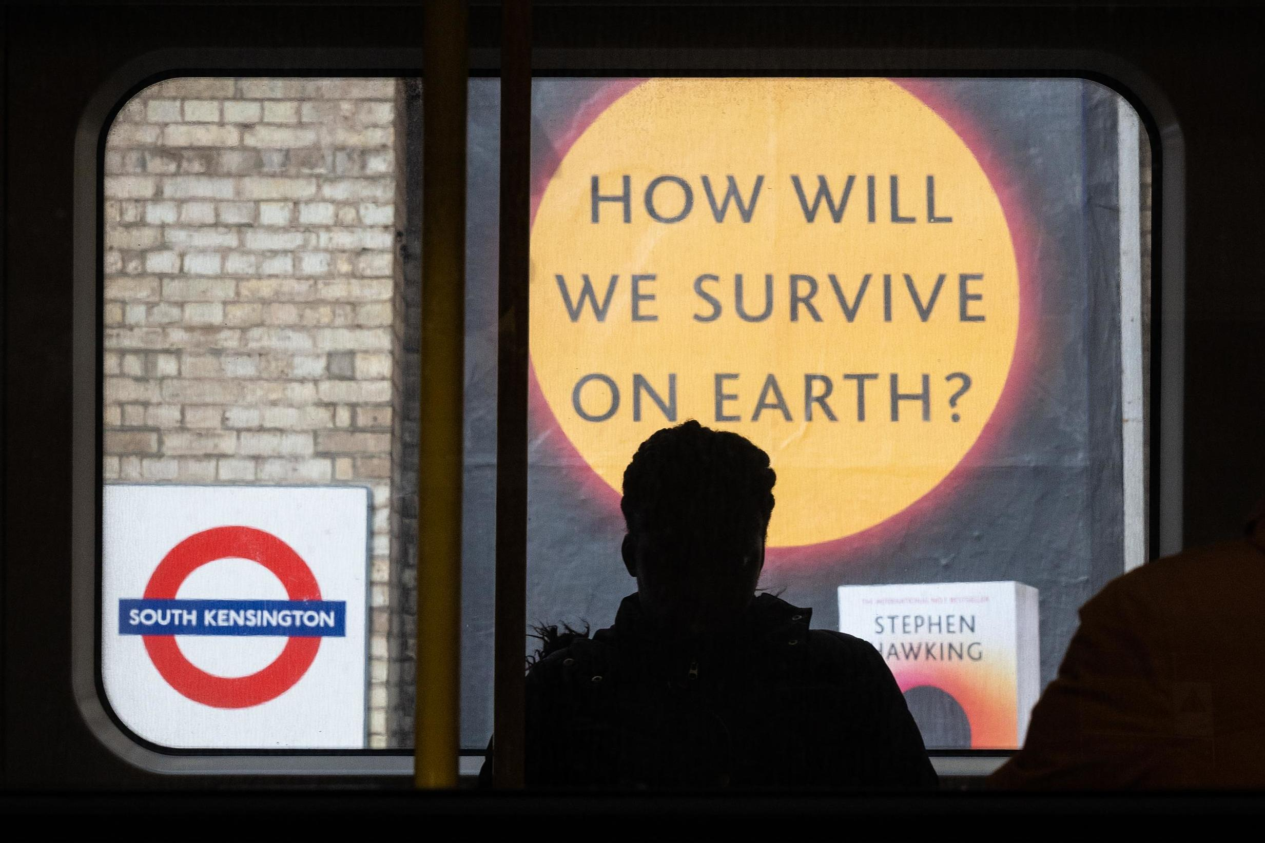 """A sign advertising a book titled """"How Will We Survive On Earth?"""" is seen on an underground station platform"""