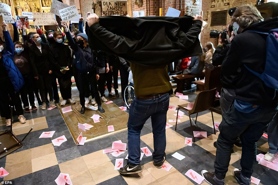 A man stands in the middle of a Poznan church with his fists raised after leaflets with a feminist symbol adopted by the protesters were strewn across the floor in protest of Poland's restrictive abortion laws