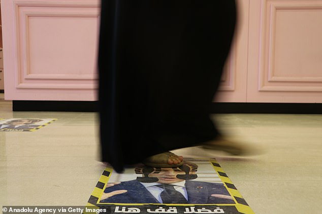 A woman walks on Macron's head in the store in Tripoli today amid anger in Libya at the French president's recent statements