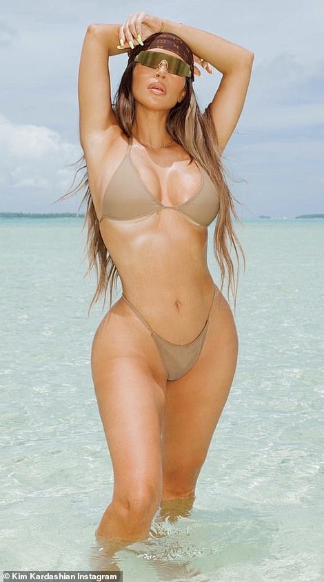 The best shape of her life:Kim had on a very small nude string bikini as she went knee deep in the crystal light blue waters on a white sand beach