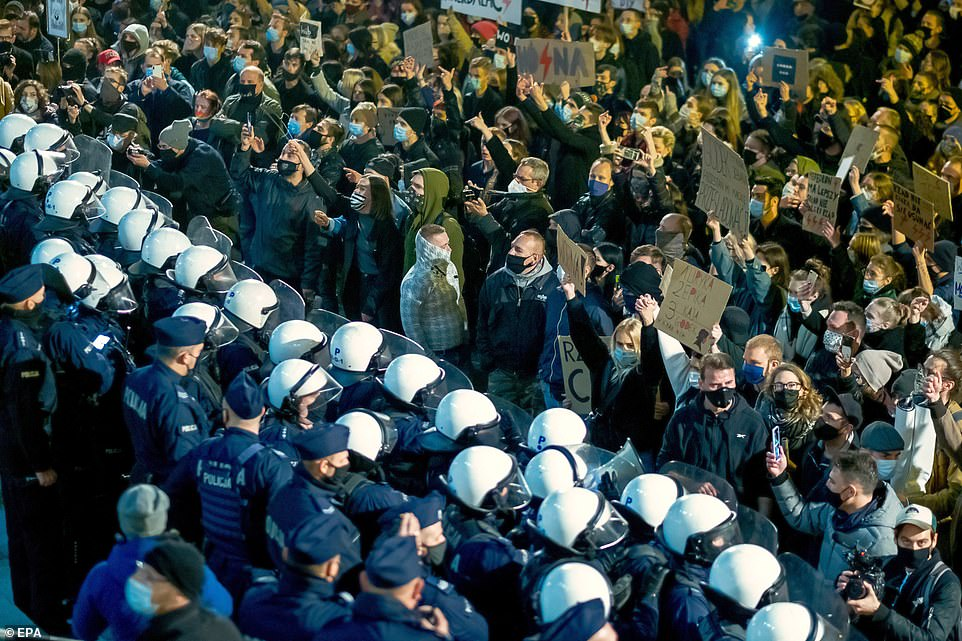 Protests took place across the country, with many being confronted by lines of police. Pictured:People stand in front of a Police cordon as they take part in a protestin front of the Christ the King Archcathedral in Katowice, southern Poland