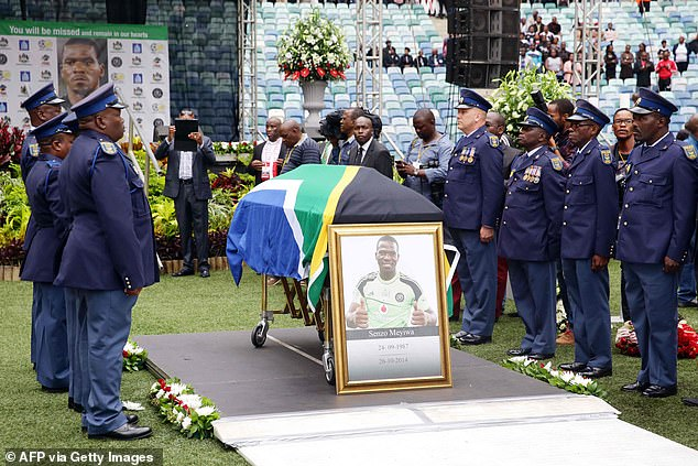 South African police officers stand guard over Meyiwa's coffin during his funeral at a stadium in Durban in 2014